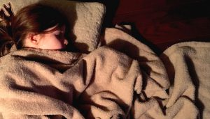 A young child sleeping with a weighted blanket. Image: Bones64 from CCO.