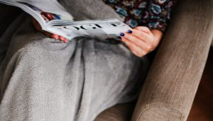 A woman relaxing with a magazine with a weighted blanket on her legs. Photo: Jacek Dyleg on Unsplash.com.