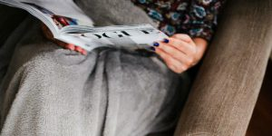 A woman relaxing with a magazine with a weighted blanket on her legs.