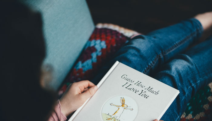 A child reading with a book on their lap. Photo by Annie Spratt on Unsplash.